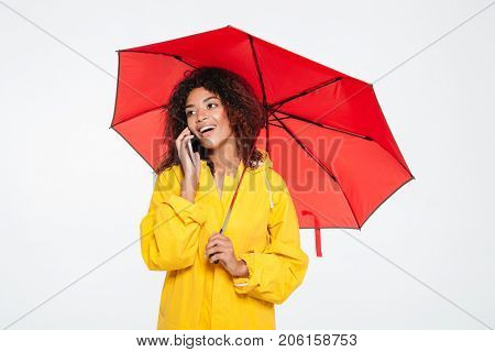 Beauty happy african woman in raincoat hiding under umbrella while talking by the smartphone and looking away over white background