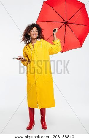 Full length image of smiling african woman in raincoat hiding under umbrella and listening music while looking away over white background