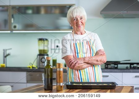 Senior woman cooking in the kitchen - eating and cooking healthy for her family; putting some potates in the oven, enjoying active retirement (shallow DOF; color toned image)