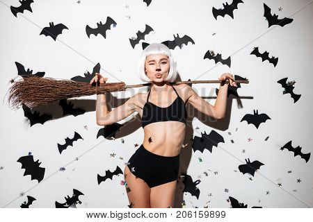 Image of attractive young woman in halloween costume cat on party over white background with broom. Looking camera.
