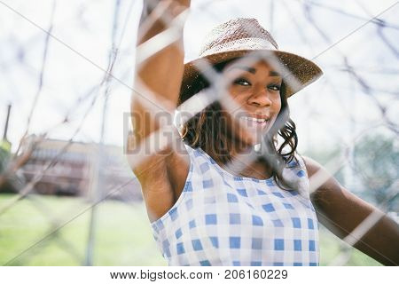 Woman Wearing Sunhat While Standing Behind Fence