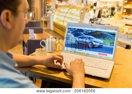 MOSCOW, RUSSIA - SEP 16, 2016: man spectacled looking keyboarding on laptop computer in cafe with Tesla auto dealer website on monitor, car on monitor