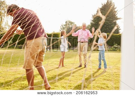 Granddad, dad and pre-teen kids playing football
