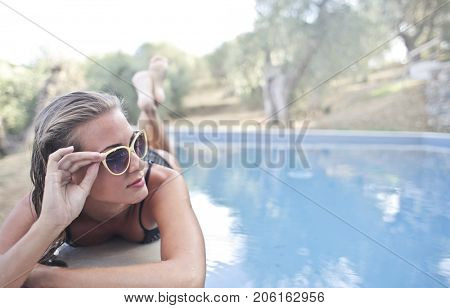 Rich girl lying by the pool