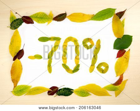 Word 70 percent made of autumn leaves inside of frame of autumn leaves on wood background. Seventy percent sale. Autumn sale template