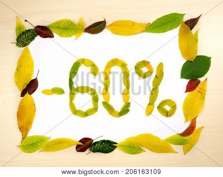 Word 60 percent made of autumn leaves inside of frame of autumn leaves on wood background. Sixty percent sale. Autumn sale template