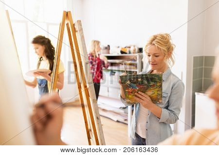 art school, creativity and people concept - woman artist with easel, paint brush and palette painting at studio