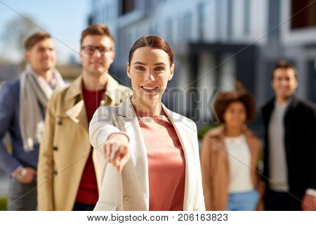 business, choice and corporate concept - happy smiling woman pointing finger at you with international group of people on city street