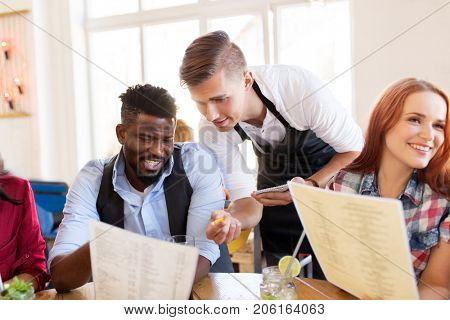 service and people concept - group of happy international friends with menu and drinks and waiter with notepad receiving order at bar or restaurant