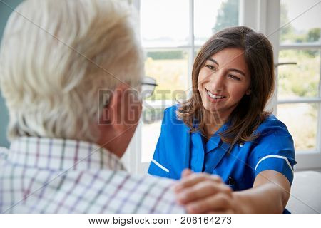 Over shoulder view of nurse on home visit with senior man