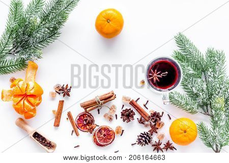 Hot mulled wine or grog cooking for new year celebration with oranges and spices ingredients on white table background flat lay