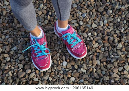 pink sports shoes of woman on gravel