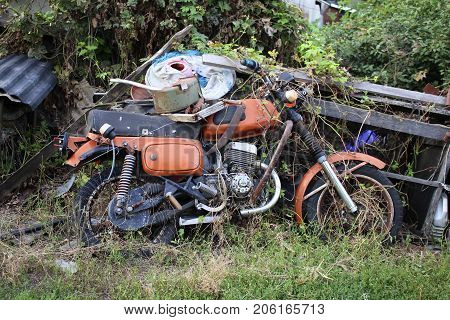 Old abandoned orange motorcycle against the background of old boards of overgrown grapes