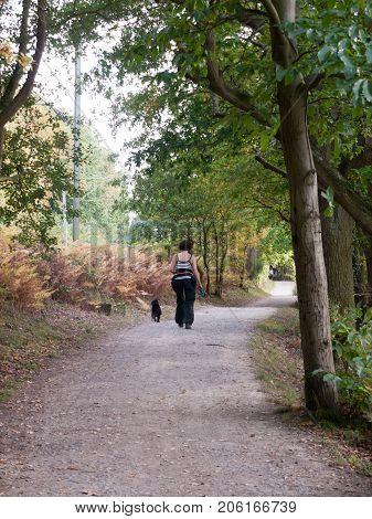 Woman Walking Dog Down Country Path Ramble
