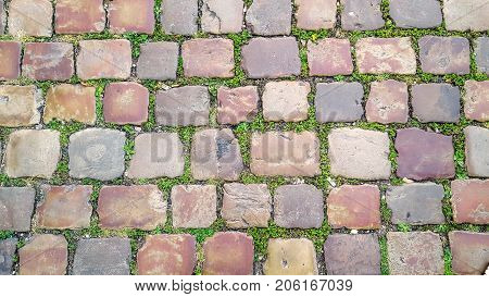Cobblestone street with grass between the stones, texture or background.