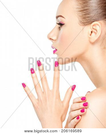 Profile face of a girl with pink nails. Fashion model posing on white background
