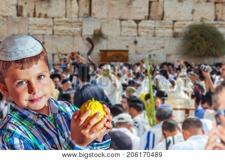 Beautiful Jewish boy in white skullcap, with etrog. Autumn Jewish holiday Sukkot. People in white Taliths pray at the Western Wall of the Temple