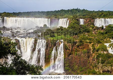The concept of exotic and extreme tourism. Waterfalls from Iguazu Falls. Powerful two-stage waterfall creates a watery dust and a rainbow