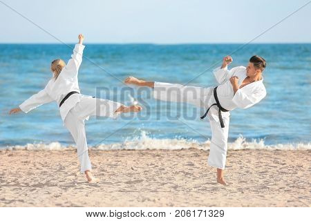 Young man and woman practicing karate outdoors