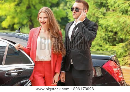 Young businesswoman with bodyguard near car outdoors