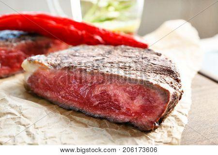 Cut rare steak on paper, closeup