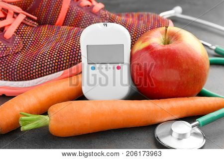 Composition with digital glucometer, carrots and apple on dark background. Diabetes concept