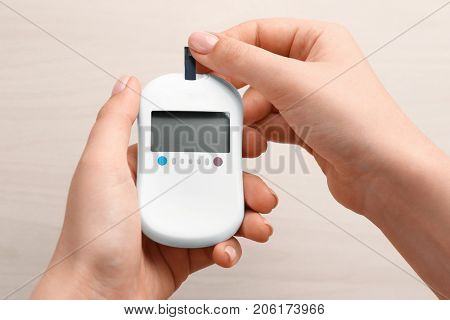 Woman's hands using digital glucometer on light background. Diabetes concept