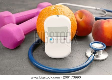 Composition with digital glucometer, stethoscope and fresh fruits on dark background. Diabetes concept