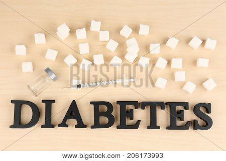 Composition with word Diabetes, sugar cubes and syringe on light background