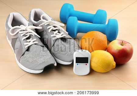 Composition with digital glucometer, fruits and sport inventory on light background. Diabetes concept