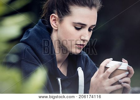 Beautiful sad depressed girl teenager female young woman drinking takeaway coffee outside