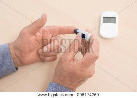 Man taking blood sample with lancet pen on wooden background