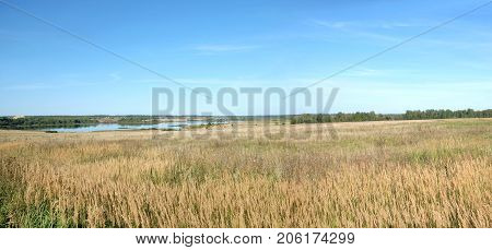 Beautiful countryside landscape with hills, lake, a village and christian church far away in sunny summer day