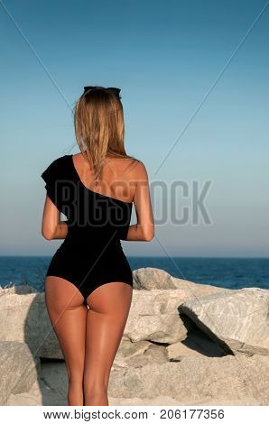 Beautiful girl in a black swimsuit on the beach. Sexy tanned buttocks on sea beach