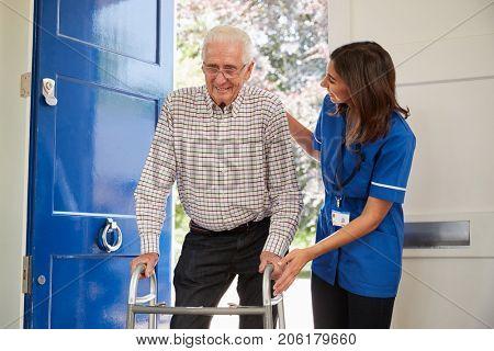 Nurse helps senior man using walking frame at home, close up