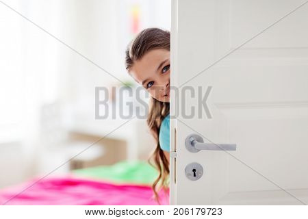 childhood, fun and people concept - happy smiling beautiful girl hiding behind door at home