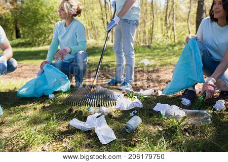 volunteering, people and ecology concept - group of happy volunteers with garbage bags and rack cleaning area in park