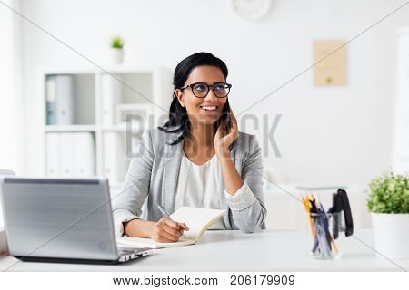 business, technology, communication and people concept - happy smiling businesswoman or secretary with notebook calling on smartphone at office