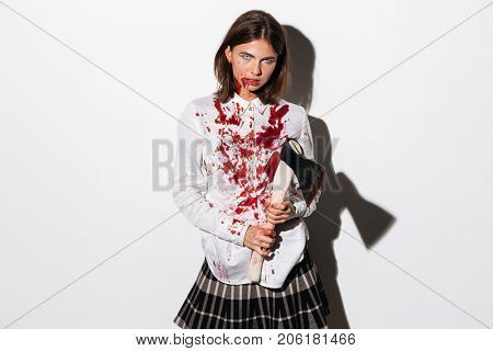Dreadful zombie woman holding an axe and looking at camera isolated over white background