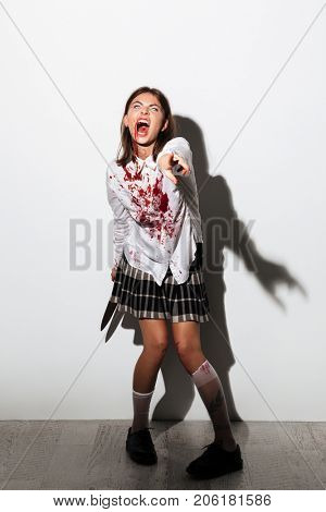 Spooky female zombie covered with blood holding a large knife and pointing at camera isolated over white background