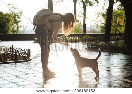 Side view of happy brunette woman in autumn clothes and eyeglasses playing with her dog in park