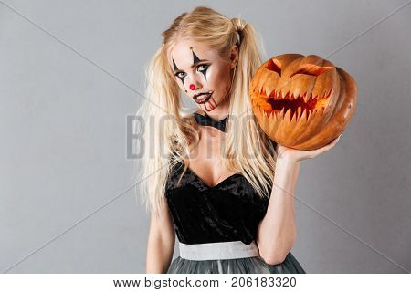 Young blonde woman in halloween clown make-up and blood streaks holding curved pumpkin and looking at camera isolated over gray background