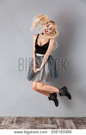 Full length portrait of a happy crazy blonde woman in halloween clown make-up and blood streaks jumping and looking at camera isolated over gray background