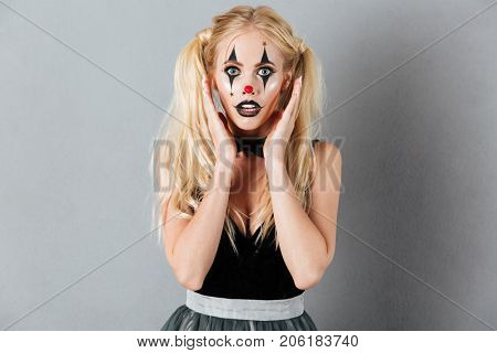 Portrait of a surprised scared blonde woman in halloween clown make-up posing while standing and looking at camera isolated over gray background