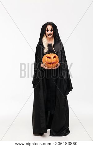 Full length portrait of a smiling blonde woman in halloween make-up and black robe holding curved pumpkin and looking at camera isolated over white background