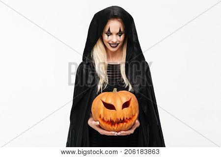 Portrait of a scary evil blonde woman in halloween make-up and black robe holding curved pumpkin isolated over white background