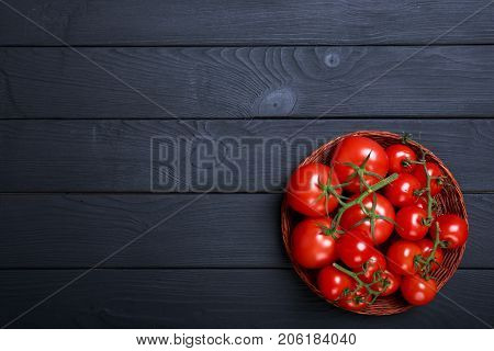 Top view of wicked bowl full of beautiful, red, ripe, tomatoes on a dark wooden background. Juicy tomato vegetables on a table. Copy space.