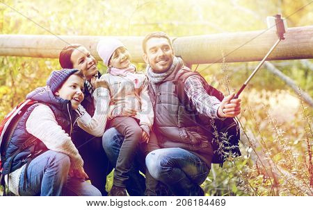 travel, tourism, hike and technology concept - happy family with backpacks taking picture by smartphone and selfie stick in woods
