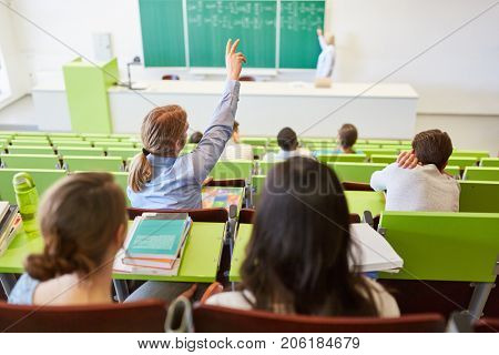 Student lifts hand and answers question in university lecture