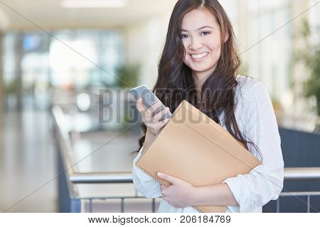 Woman as happy asian student holding smartphone and notebook in university